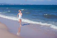 Mulher livre bonita feliz que corre no salto da praia brincalhão foto de stock