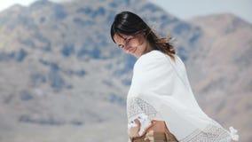Mulher local livre feliz nova bonita que olha para trás na câmera que sorri e que flerta no lago ensolarado do deserto de sal em  filme