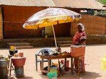 A mulher local não identificada vende vegetais em uma vila em Guine imagem de stock