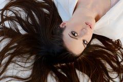 Mulher longa bonita do cabelo que coloca no assoalho fotos de stock