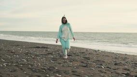 A mulher louca está vestindo o traje do kigurumi do unicórnio está correndo sobre a praia vídeos de arquivo