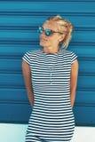 Mulher loura à moda nova que levanta no obturador azul do rolo exterior fotos de stock
