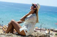 Mulher loura à moda que sorri e que usa o smartphone Fotografia de Stock