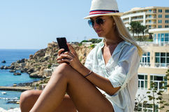 Mulher loura à moda que sorri e que usa o smartphone Foto de Stock