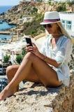 Mulher loura à moda que sorri e que usa o smartphone Imagens de Stock