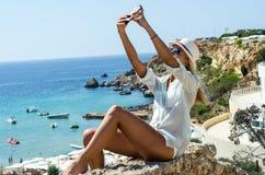 Mulher loura à moda que sorri e que usa o smartphone Imagens de Stock Royalty Free