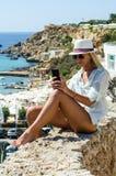 Mulher loura à moda que sorri e que usa o smartphone Foto de Stock Royalty Free