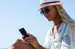Mulher loura à moda que sorri e que usa o smartphone Fotografia de Stock Royalty Free