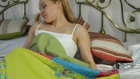 A mulher loura acorda, olha o despertador e esconde-o sob o descanso 4K vídeos de arquivo