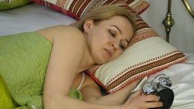 A mulher loura acorda, olha o despertador e esconde-o sob o descanso Movimento lento video estoque