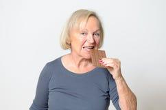 Mulher loura adulta que come a barra de chocolate no fim acima Imagem de Stock