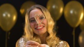Mulher loura agradável que mostra a luz de bengal coração-dada forma na câmera, celebração vídeos de arquivo