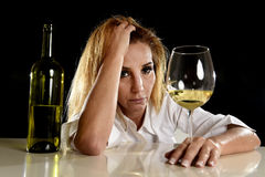 Mulher loura alcoólica bêbada apenas na manutenção de sofrimento bebendo deprimida desperdiçada do vidro de vinho branco Fotografia de Stock Royalty Free