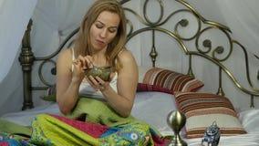 A mulher loura alegre está comendo uma salada deliciosa em uma cama, café da manhã saudável 4K filme