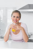 Mulher loura alegre que come o suco de laranja Imagem de Stock