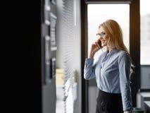 Mulher loura alegre que usa o smartphone para uma comunicação empresarial imagem de stock royalty free