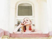 Mulher loura alegre suducive bonita que olha do balcão Fotografia de Stock Royalty Free