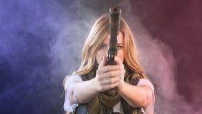 A mulher loura armada dispara com arma em um alvo na escuridão com nuvens de fumo, movimento lento vídeos de arquivo