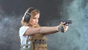 A mulher loura armada dispara com arma em um alvo na escurid?o com nuvens de fumo Movimento lento vídeos de arquivo