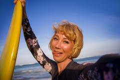 Mulher loura atrativa e feliz nova do surfista no roupa de banho que guarda a placa de ressaca na praia que toma o SMI da imagem  imagem de stock royalty free