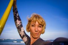 Mulher loura atrativa e feliz nova do surfista no roupa de banho que guarda a placa de ressaca na praia que toma o SMI da imagem  imagens de stock royalty free