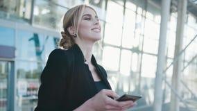 A mulher loura atrativa em um olhar preto à moda, suportes pelo centro de negócio, recebe a mensagem, lê-a, respira para fora video estoque