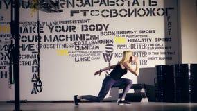 A mulher loura atrativa nas caneleiras e na parte superior executa o exercício, saltos, no gym Exercício da classe da aptidão car filme