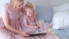 A mulher loura atrativa nova com sua filha encantador pequena no rosa veste a observação de algo na tabuleta que senta-se sobre video estoque