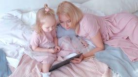 A mulher loura atrativa nova ensina sua filha encantador pequena em vestidos cor-de-rosa usando uma tabuleta que coloca na cama video estoque