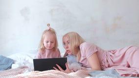 A mulher loura atrativa nova ensina sua filha encantador pequena em vestidos cor-de-rosa usando uma tabuleta que coloca na cama filme