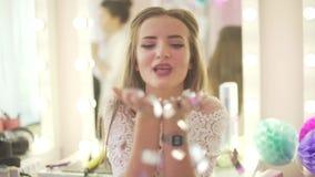 Mulher loura atrativa nova no brilho de prata da celebração do partido dos confetes dos sopros brancos do vestido do laço das mão filme