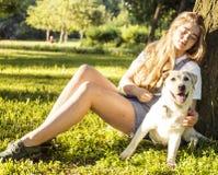 Mulher loura atrativa nova que joga com seu cão no parque verde Foto de Stock