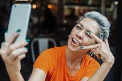 Mulher loura atrativa que faz o selfie no café e que mostra o sinal da vitória foto de stock