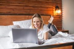 Mulher loura atrativa que usa o laptop ao encontrar-se na cama imagem de stock