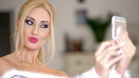Mulher loura atrativa 'sexy' que levanta para um selfie video estoque