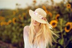 A mulher loura bonita com cabelo longo e o sunhat no girassóis rurais colocam imagem de stock