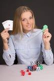 Mulher loura bonita com cartões de jogo e microplaquetas de pôquer sobre a GR Imagens de Stock