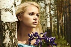 Mulher loura bonita com flores azuis em uma floresta Imagens de Stock