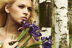Mulher loura bonita com flores azuis em uma floresta Foto de Stock Royalty Free