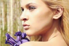 Mulher loura bonita com flores azuis em uma floresta Foto de Stock
