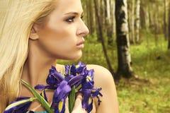 Mulher loura bonita com flores azuis em uma floresta Fotos de Stock
