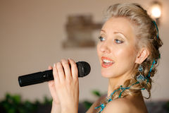 Mulher loura bonita com microfone Fotografia de Stock Royalty Free