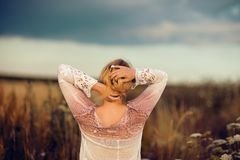 Mulher loura bonita com o cabelo longo que está em um campo de flor rural fora, aumentando seu cabelo foto de stock royalty free