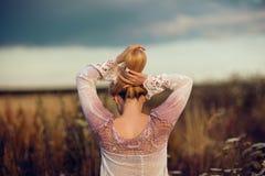 Mulher loura bonita com o cabelo longo que está em um campo de flor rural fora, aumentando seu cabelo foto de stock