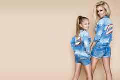Mulher loura bonita com sua filha em um revestimento e no short da sarja de Nimes Modelos de forma na roupa das calças de brim Fotos de Stock Royalty Free