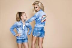 Mulher loura bonita com sua filha em um revestimento e no short da sarja de Nimes Modelos de forma na roupa das calças de brim Imagens de Stock Royalty Free