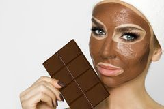 Mulher loura bonita com uma máscara facial, termas da beleza Máscara protetora do chocolate fotografia de stock royalty free