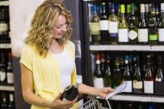 Mulher loura bonita de sorriso que olha o bloco de notas e que tem em suas mãos uma garrafa de vinho Fotos de Stock Royalty Free