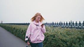 Mulher loura bonita bonita do moderno com longboard do skate usando seu telefone celular do smartphone para a consultação, os sms filme