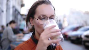 Mulher loura bonita do verão do café na bebida da bebida contentemente com espuma O visitante fêmea aprecia tomar o sorvo do capp vídeos de arquivo